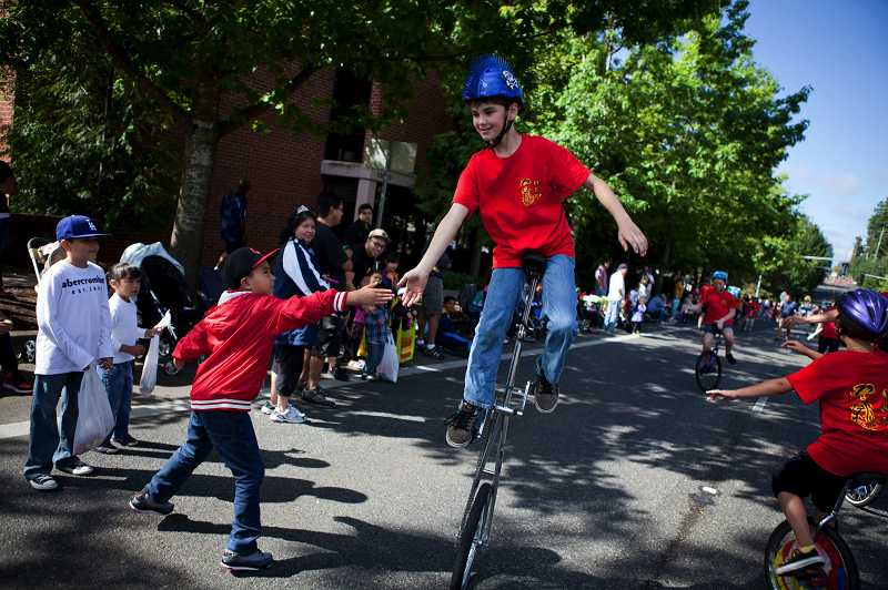 by: TIMES PHOTO: ADAM WICKHAM - Members of 'One Wheel Wonders' unicycling and juggling club interact with the crowd during the 56th annual Beaverton Celebration Parade.