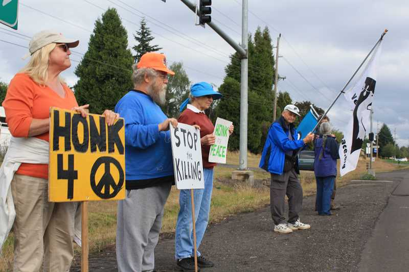 by: POST PHOTO: NEIL ZAWICKI - Susan Gates, Walt Trandum, and Mabel and Will Pool, stand along Highway 26 near Fred Meyer on Friday, Sept. 6. The group, since 2007, has held the weekly vigil to oppose war.