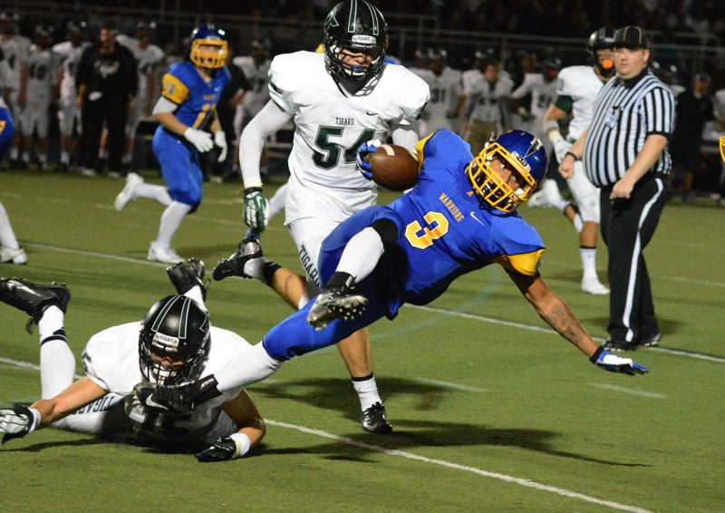 by: TIMES PHOTO: MATT SINGLEDECKER - Aloha senior running back Calvin Davis lunges for yardage.