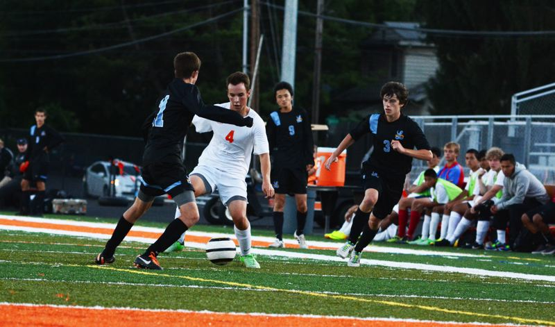 by: TIMES PHOTO: MATT SINGLEDECKER - Beaverton senior Nico Maier dribbles around a Lakeridge defender on the Beavers side of the pitch.