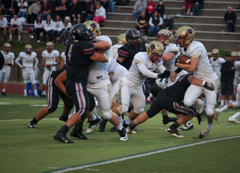 by: TIMES PHOTO: ADAM WICKHAM - Southridge running back Jacob Pruitt fights through a Tualatin tackle on Friday.