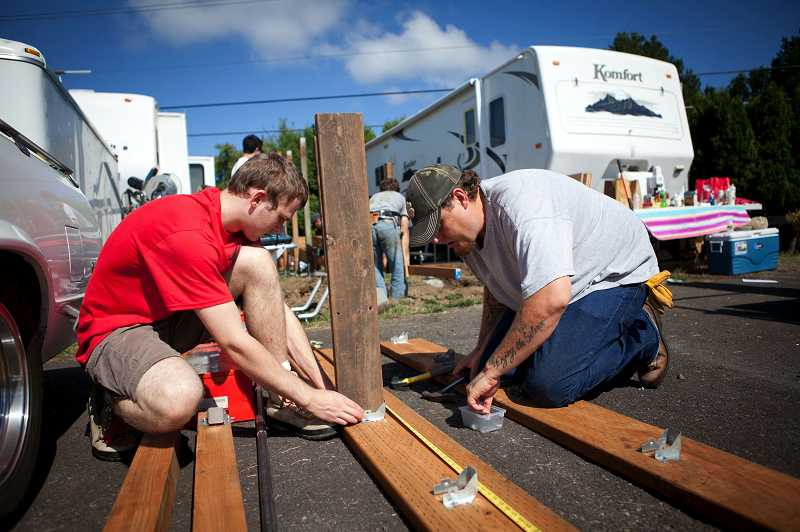 by: PHOTO FOR THE TIMES: ADAM WICKHAM - Catalyst Partnerships volunteers Daniel Small, left, and Kelly Shaw work on a a new wheelchair-accessibility ramp to Ruth Ford's mobile home in Cedar Hills.