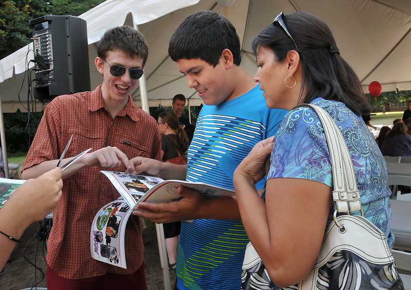 by: REVIEW PHOTO: VERN UYETAKE - Park Academy juniors Chris Wold, left, and Andrew Onofrei scan the new yearbook with parent Mary Renner.