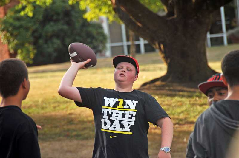 by: REVIEW PHOTO: VERN UYETAKE - Eighth-grader Henry Pope gets in some football action before sitting down to eat.