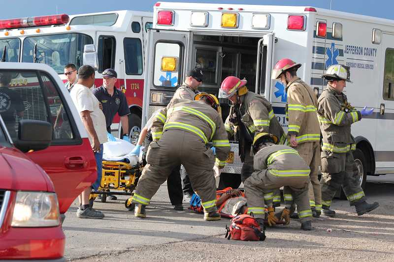 by: HOLLY M. GILL - Personnel from the Jefferson County Fire Department and Jefferson County Emergency Medical Services load driver Isaul Alberto Ruiz-Dominguez into the ambulance, following the Sept. 5 accident.