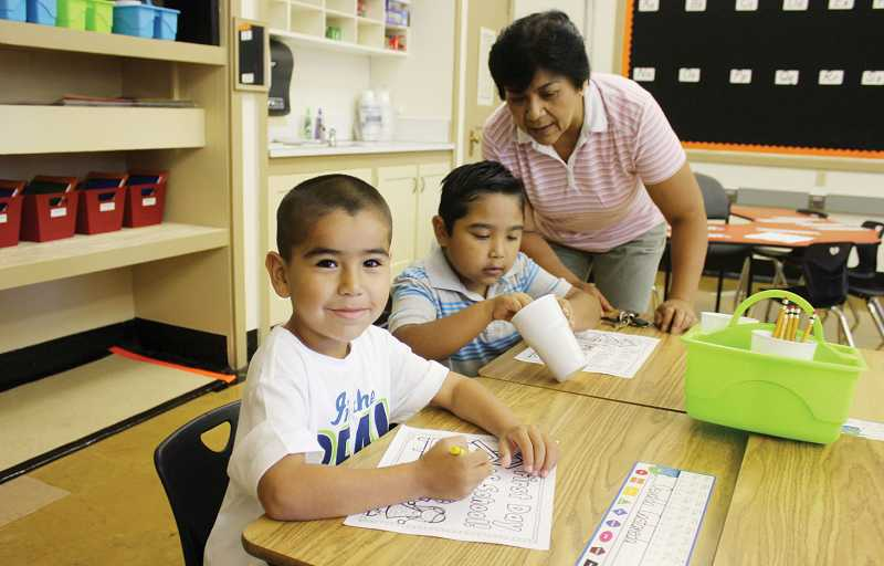 by: SUSAN MATHENY - First-graders Osvaldo Castaneda (front) and Itiel Medrano, pictured with his mother, get situated in their new classroom at Madras Primary on Monday, the first day of school for most students in the 509-J School District. The district had 1,567 students reporting on the first day.