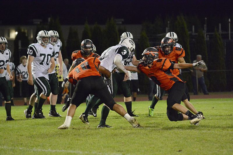 by: JOHN WILLIAM HOWARD - Lionel Sandoval (16) and Robby Backus (8) team up to take down Estacada quarterback Willie Blankenship. The Indians smothered the Rangers' offense, allowing only one scoring drive once the game had already been decided.