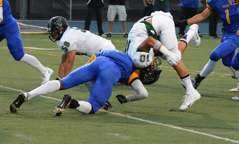 by: MATTHEW SINGLEDECKER - STAYING TOUGH -- Tigard senior running back Manu Rasmussen absorbs a hit from Aloha's Maurice McSwain in the first quarter of the Tigers' runaway 56-7 win on Friday.