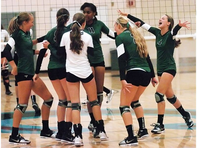 by: DAN BROOD - VICTORY DANCE -- The Tigard High School volleyball team celebrates after getting the winning point in the match against Century.