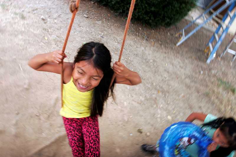 by: OUTLOOK PHOTO: JIM CLARK - Sarai, 8, plays on a tree swing in her backyard at Barberry Village.
