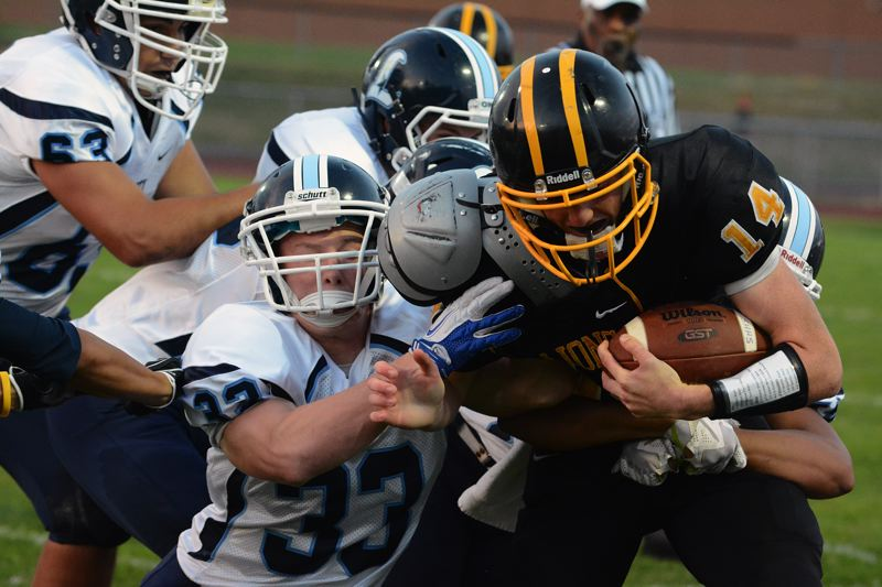 by: JOHN WILLIAM HOWARD - Lions' senior quarterback Gage Bumgargner (14) is wrapped up by the Liberty defense in the first quarter of St. Helens' 34-33 loss on Friday night. Bumgardner had more than 100 yards on the ground and in the air respectively, and finished with two touchdowns of each variety.