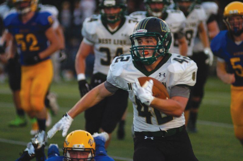 by: PAMPLIN MEDIA GROUP: DAVID BALL - West Linn senior running back Louie Germaine breaks away from a pack of Barlow tacklers during Fridays 41-28 road win. He scored all six of the Lions touchdowns.