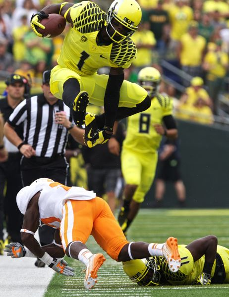 by: TRIBUNE PHOTO: JAIME VALDEZ - Josh Huff, Oregon wide receiver, hurdles a Tennessee defender during a Ducks drive.
