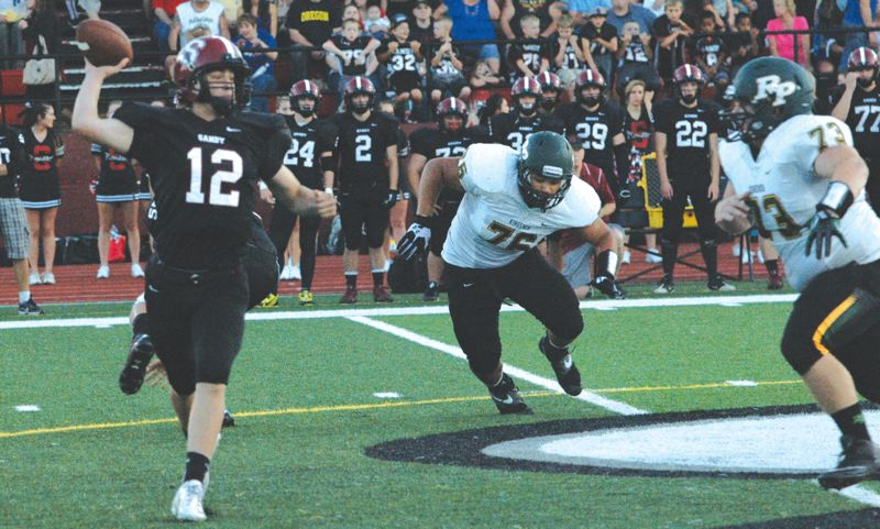 by: SANDY POST: PARKER LEE - Sandy QB Spencer Barrett rolls out to find an open receiver during Fridays win to start the NWOC season.