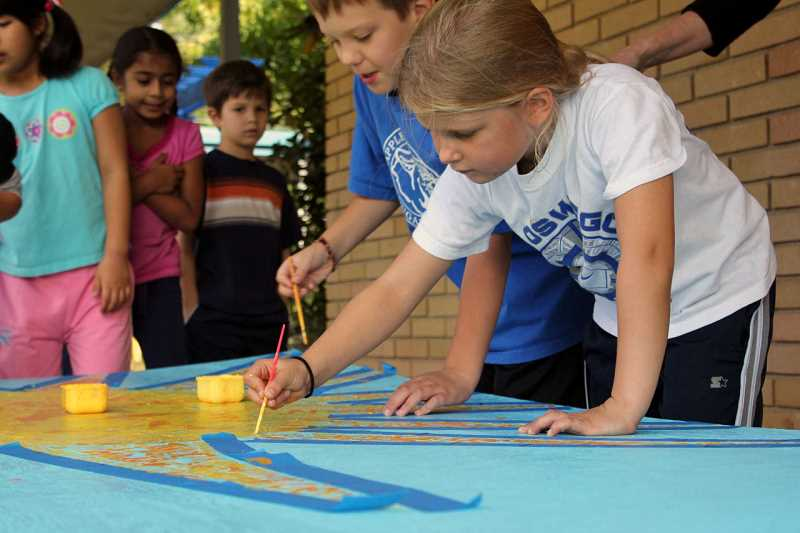 by: SUBMITTED - Former Bryant Elementary School students Owen Culver and Reese Ericson work on the mural in 2010.