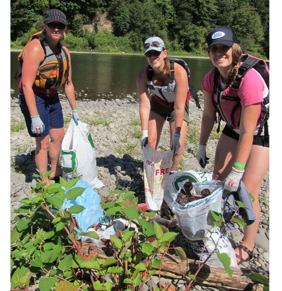by: PHOTO BY ELLEN SPITALERI - Jess Oberg, left, and sisters Molly Luettgerodt and Kim Svela clean up broken glass and gather cans, bottles, discarded flip flops and more as they clean up a small island in the middle of the river.