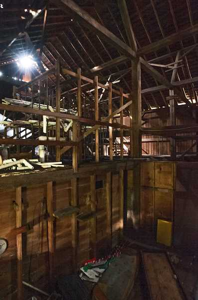 by: JOSH KULLA - This interior shot of the old barn that once belonged to the Ash family shows how it has been divided into small rooms underneath a cavernous roof and ceiling. The building has no electricity and all light comes through cracks in the walls and roof.