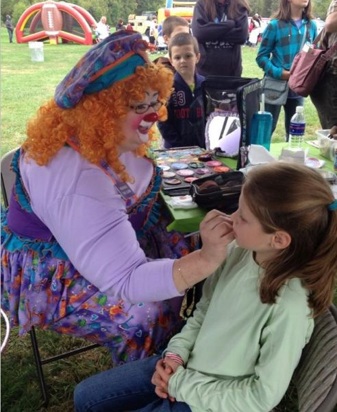 by: PHOTO BY: MRS. LISA MARELLA - Children line up for face painting as a clown adds finishing touches to Arina Rundgren during the 364th Civil Affairs Brigades Army Family Day Celebration at Happy Valley Park on Sept. 15.