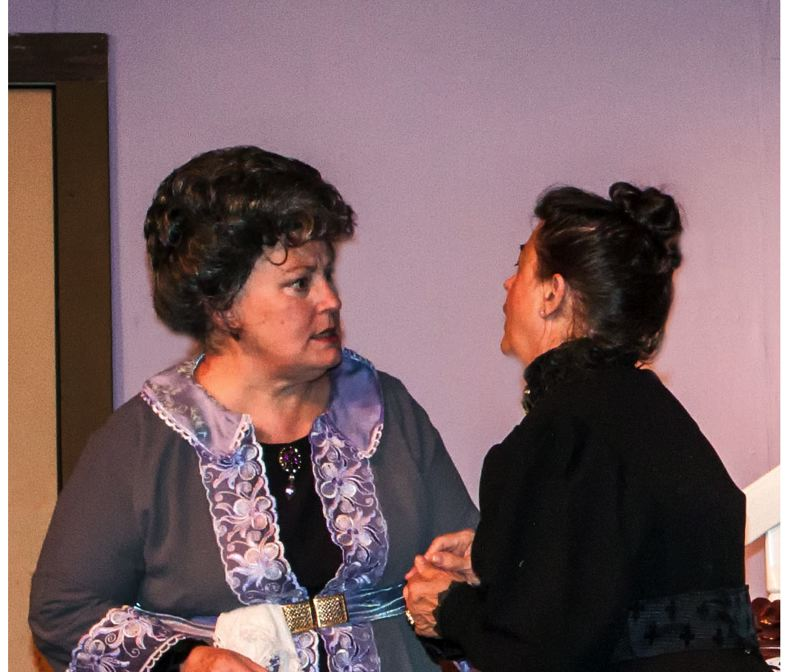 by: CONTRIBUTED PHOTO: ROD STROH - In a scene from Arsenic and Old Lace, Aunt Abby, left, portrayed by Valerie Brooks, and Aunt Martha, staged by Berta Limbaugh, discuss the next person (usually a man of the cloth) who will receive a glass of elderberry wine (spiked with the usual poison). The stage production continues at Sandy Actors Theater until Oct. 6.
