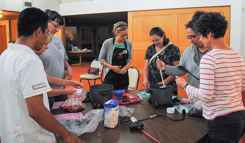 by: NEWS-TIMES PHOTO: STEPHANIE HAUGEN - The food preservation classes at the Forest Grove UCC start with a lecture and conclude with hands-on canning demonstrations. Kaely Summers of Adelante Mujeres helped out.