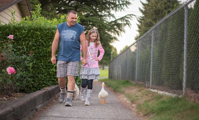 by: NEWS-TIMES PHOTO: CHASE ALLGOOD - The Lorangers of Forest Grove, including Rocky and his daughter Brittany, have made Butterscotch the duck and Lilly the Pomeranian part of their family and nightly routines.