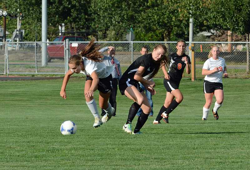 by: JOHN WILLIAM HOWARD - Scappoose center midfielder Natalie Muth (left) takes a tumble in the second half of Scappoose's victory over Molalla. The Tribe defeated Molalla 2-1 on Tuesday, Sept. 17 for their first victory of the season.