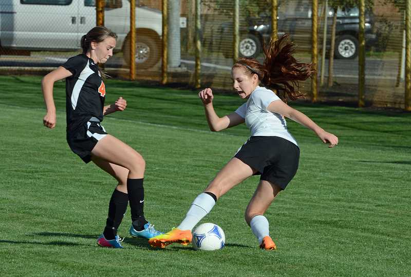 by: JOHN WILLIAM HOWARD - Scappoose junior Madison Verzino (at right) makes a move around Molalla's Audrey Bever during Scappoose's 2-1 victory on Tuesday, Sept. 17.