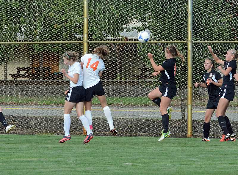by: JOHN WILLIAM HOWARD - Junior Eleanor Jones (14) heads the ball toward the net for a goal early in the second half. Jones' goal was the difference maker in the 2-1 victory over Molalla on Tuesday, Sept. 17.