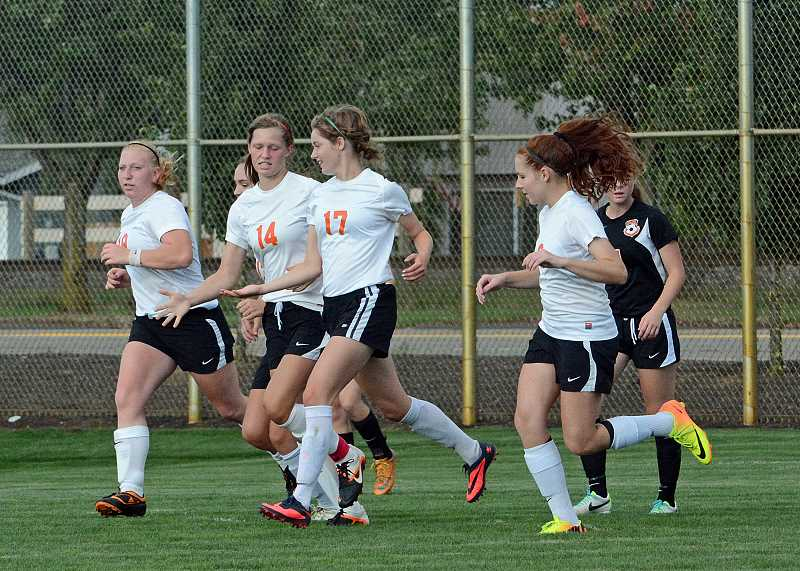 by: JOHN WILLIAM HOWARD - Scappoose players celebrate a second half goal by Eleanor Jones. The Tribe got a goal in each half to defeat Molalla 2-1 on Tuesday, Sept. 17.