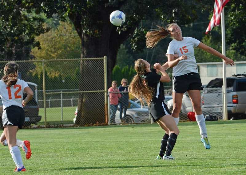 by: JOHN WILLIAM HOWARD - Senior centerback Jenny Vardanega heads the ball away from an oncoming attacker. Scappoose defeated Molalla 2-1 for their first victory on Tuesday, Sept. 17.