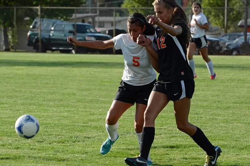 by: JOHN WILLIAM HOWARD - Addie Buchanan (5) fights Kelsey Brandt for the ball in the second half of the Tribe's 2-1 victory on Tuesday afternoon. Brandt score the lone goal for Molalla in the first half on Sept. 17.