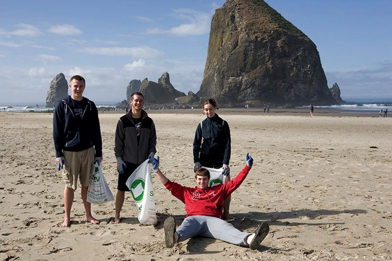 by: PHOTO COURTESY OF GARY LOVELESS - Teenage volunteers gather litter at Cannon Beach during the 2012 Beach and Riverside Cleanup.