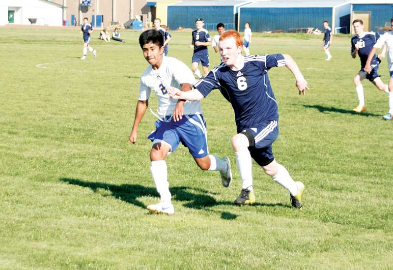 by: PHIL HAWKINS - Gervais junior Miguel Morales (left) chases down the ball in Wednesdays 5-2 loss at home against the Riverdale Mavericks.