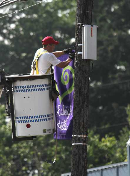 by: TIMES PHOTO: JONATHAN HOUSE - Alfonso Sanchez puts up a new Raleigh Hills banner along Scholls Ferry Road at Beaverton-Hillsdale Highway on Friday.