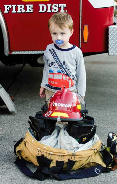 by: RAY HUGHEY - Brendan Vroman, 2, waits while his firefighter dad, Tighe Vroman, gets ready for the memorial program.
