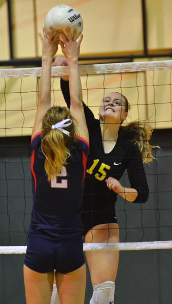 by: VERN UYETAKE - West Linn's Shawna Erickson looks to knock a spike through a Lake Oswego blocker. Erickson played a big role in helping the Lions build an early lead against the Lakers.