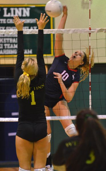 by: VERN UYETAKE - Lake Oswego's Taylor Beckman goes for a kill against a West Linn blocker in Tuesday's league match at West Linn High School.