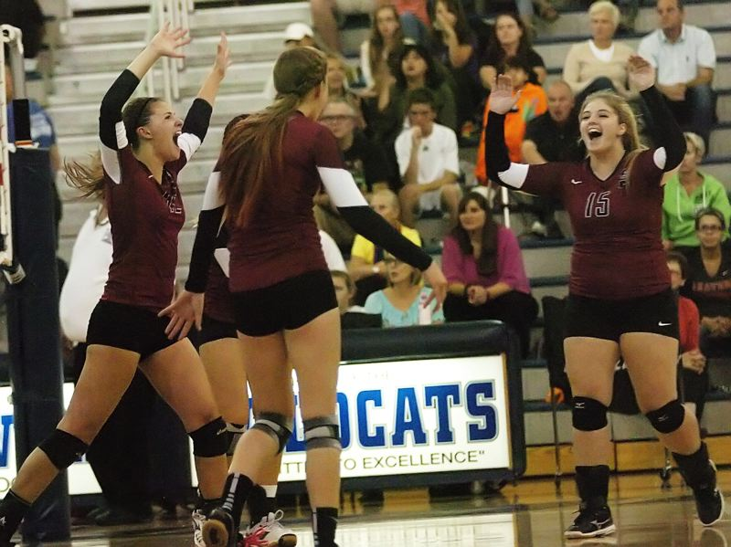 by: DAN BROOD - SHERWOOD CELEBRATION -- The Lady Bowmen celebrate after scoring a point in Tuesday's match at Wilsonville.