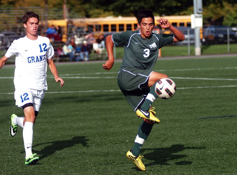 by: DAN BROOD - KEEPING CONTROL -- Tigard senior Javier Sanchez-Figueroa (3) controls the ball as Grant's Joey Kenney closes in during Tuesday's match.
