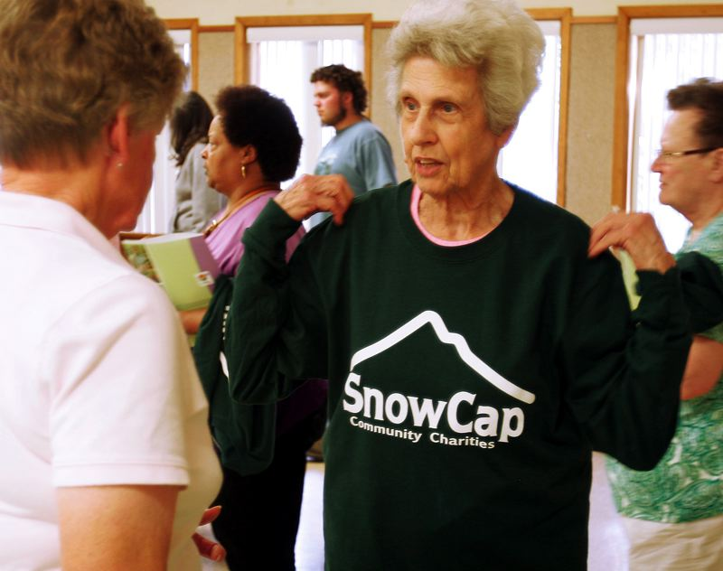 by: OUTLOOK PHOTO: JIM CLARK - Volunteer Alice Dickenson tries on her new SnowCap shirt following a training session Friday, Sept. 13.