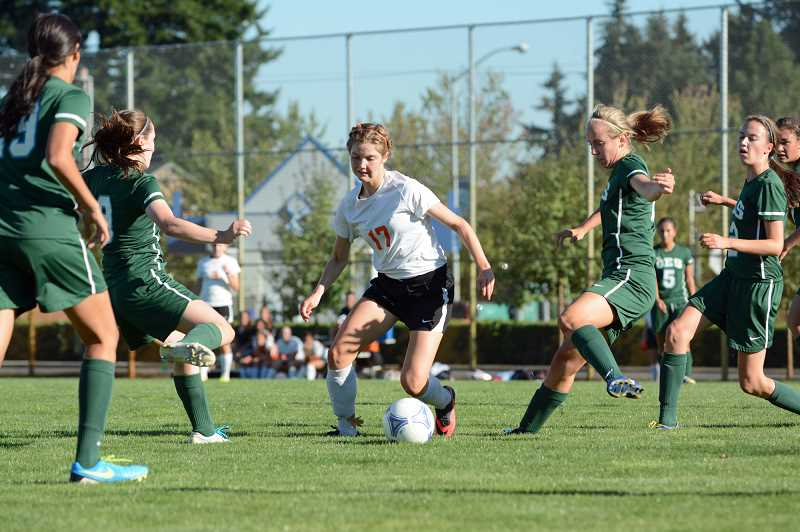 by: JOHN WILLIAM HOWARD - Indians' midfielder Lucy Davidson dribbles through a wave of oncoming attackers. The Indians gave up three goals in the first half and a goal in the second in a shutout to Oregon Episcopal School on Thursday, Sept. 19.