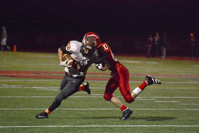 by: JOHN WILLIAM HOWARD - Nick Rust fights off a defender during the first half of Scappoose's 22-14 loss to Central on Friday, Sept. 20.