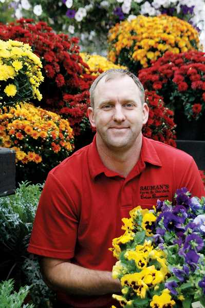 by: PHIL HAWKINS - Brian Bauman of Bauman Farms displays a flat of pansies while sitting in front of a stand of Belgian mums. Pansies and mums are two flowering plants that can add color to a garden, yet are hearty enough to thrive in Oregons climate.