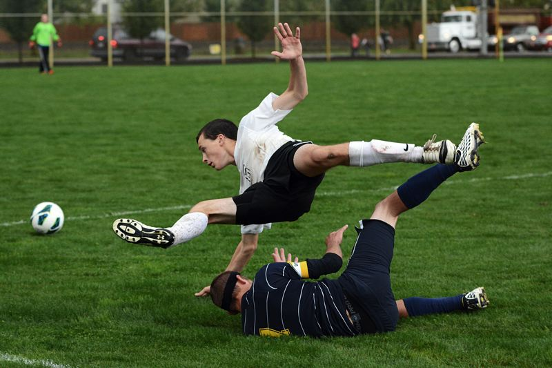by: JOHN WILLIAM HOWARD - Scappoose junior Asa Flanagan tumbles over a Banks defender on Tuesday afternoon. Flanagan didn't score, but assisted the first half goal that gave the Indians their first lead of the season.