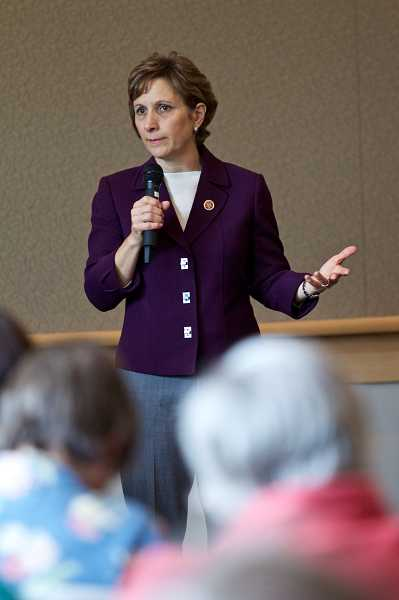 by: TIMES PHOTO:JAIME VALDEZ - Congresswoman Suzanne Bonamici responds to citizen Ralph Robins concerns about Syria during a town hall meeting in the Tualatin Public Library Community Room.