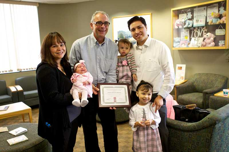 by: TIMES PHOTO: JAIME VALDEZ - Tualatin Mayor Lou Ogden poses with the Moreno family to recognize baby Arianni for being the 100th baby born in Tualatin at Legacy Meridian Parks Family Birth Center. Pictured from left: mom Sophia, baby Arianni, her sisters Reyna Elena, and dad, Reyes.