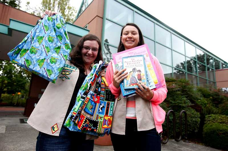 by: TIMES PHOTO: JONATHAN HOUSE - Tigard Girl Scouts Emma Barbee and Sabrina McKenzie hold up some of the numerous childrens books that they collected for recent donation drive. Proceeds go to the Tigard Police Department who will put the books into each squad car, to be used when on emergency calls involving children.