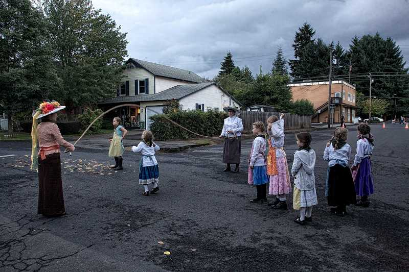 by: SUBMITTED PHOTO: GLEN BLEDSOE - Erin Ruff and Lydia Bollinger played an old-fashioned jump rope game with a group of children at the Willamette Living History Tour.
