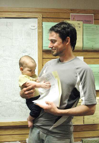 by: ISABEL GAUTSCHI - Sean Rooney of Milwaukie holds his free use mushroom permit as baby Everett reaches for it.