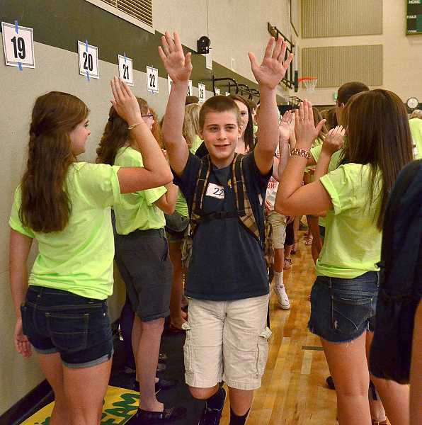 by: TIDINGS PHOTO: VERN UYETAKE - Freshman Ben Gans exits the long line of teachers and Link Crew members greeting the new freshmen during freshman orientation Sept. 3.